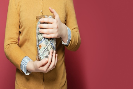 Woman holding a jar of money